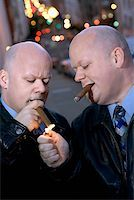Identical twins smoking cigars Stock Photo - Premium Royalty-Freenull, Code: 604-00759610