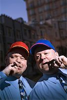 Identical twins in baseball caps smoking cigars Stock Photo - Premium Royalty-Freenull, Code: 604-00759611