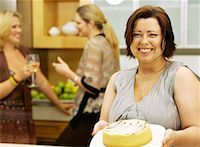 Portrait of a young woman holding a cake on a plate Stock Photo - Premium Royalty-Freenull, Code: 618-00785651