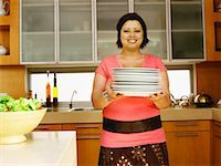 Portrait of a young woman holding plates in a kitchen Stock Photo - Premium Royalty-Freenull, Code: 618-00785654