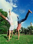 Side profile of two sisters doing cartwheels on the grass Stock Photo - Premium Royalty-Freenull, Code: 618-00786263