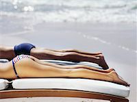 Low section view of a young couple sunbathing on the beach Stock Photo - Premium Royalty-Freenull, Code: 618-00786574