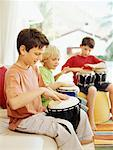Side angle view of three boys playing the bongo drums Stock Photo - Premium Royalty-Free, Artist: Ed Gifford, Code: 618-00786643