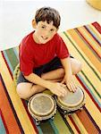 High angle view of a boy playing the bongo drums Stock Photo - Premium Royalty-Free, Artist: Carl Valiquet, Code: 618-00786645