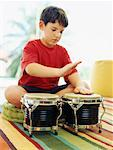 Boy playing the bongo drums Stock Photo - Premium Royalty-Free, Artist: Westend61                , Code: 618-00786646
