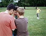 Boys (9-12) in park whispering in huddle, girl (9-11) in background Stock Photo - Premium Royalty-Free, Artist: Rolf Bruderer, Code: 613-00810525