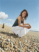 Young woman crouching on pebble beach, smiling, portrait Stock Photo - Premium Royalty-Freenull, Code: 613-00810639