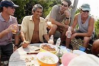 Group of men having drinks around table outdoors, smiling Stock Photo - Premium Royalty-Freenull, Code: 613-00811128