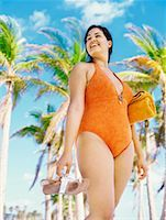 Low angle view of a young woman standing on the beach, holding a towel and flip-flops Stock Photo - Premium Royalty-Freenull, Code: 618-00832907