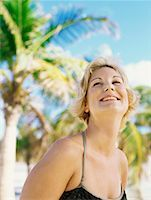 Portrait of a young woman standing on the beach, smiling Stock Photo - Premium Royalty-Freenull, Code: 618-00832930