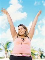 Close-up of a young overweight woman standing on the beach with her arms raised Stock Photo - Premium Royalty-Freenull, Code: 618-00832938