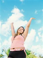 Low angle view of a young overweight woman standing on the beach with her arms raised Stock Photo - Premium Royalty-Freenull, Code: 618-00832939