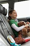 Girl (6-8 years) sitting with soft toys on rear seat of car, smiling, side view Stock Photo - Premium Royalty-Free, Artist: Blend Images, Code: 613-00834383