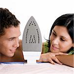 Close-up of a young couple looking at each other with an iron between them Stock Photo - Premium Royalty-Free, Artist: Cusp and Flirt, Code: 625-00838113