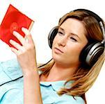 Close-up of a businesswoman wearing headphones looking at a CD case Stock Photo - Premium Royalty-Free, Artist: Stellar Stock, Code: 625-00840957