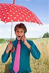 Young Man Using Cell Phone and Holding Umbrella    Stock Photo - Premium Rights-Managed, Artist: Michael A. Keller, Code: 700-00847425