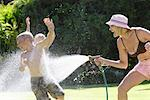 Mother Spraying Kids With Garden Hose