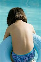 Rear view of a girl in an inflatable ring Stock Photo - Premium Royalty-Freenull, Code: 625-00849751