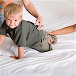 Boy crawling on a bed Stock Photo - Premium Royalty-Freenull, Code: 625-00850251