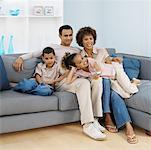 Front view of parents and two children sitting on sofa (9-11) Stock Photo - Premium Royalty-Freenull, Code: 627-00852865