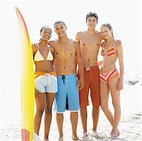 Front view portrait of four young people standing at beach and holding surfboard Stock Photo - Premium Royalty-Freenull, Code: 627-00856621