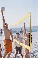 Group of young people playing beach volley