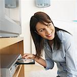 portrait of young woman playing a DVD Stock Photo - Premium Royalty-Free, Artist: Glowimages               , Code: 627-00860795