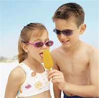 Sister licking her brothers ice pop Stock Photo - Premium Royalty-Freenull, Code: 627-00862130