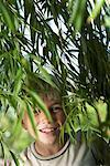 Boy Looking Through Foliage    Stock Photo - Premium Royalty-Free, Artist: Masterfile, Code: 600-00866543