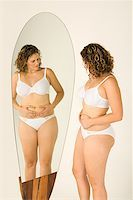 Woman looking at stomach in the mirror Stock Photo - Premium Royalty-Freenull, Code: 614-00892447