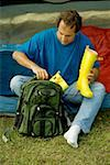 High angle view of a mature man packing galoshes into a backpack Stock Photo - Premium Royalty-Freenull, Code: 625-00900121