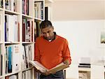 Man looking at book by bookshelf Stock Photo - Premium Royalty-Free, Artist: Marie Blum, Code: 613-00907954
