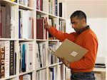 Man by bookshelf looking at book Stock Photo - Premium Royalty-Free, Artist: Blend Images, Code: 613-00908254