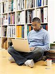 Man leaning against bookshelf, laptop computer on lap Stock Photo - Premium Royalty-Free, Artist: Marie Blum, Code: 613-00908522