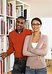 Couple standing by bookshelf, smiling, portrait Stock Photo - Premium Royalty-Free, Artist: Blend Images, Code: 613-00908593