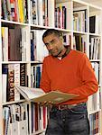 Man holding book by bookshelf, portrait Stock Photo - Premium Royalty-Free, Artist: Marie Blum, Code: 613-00908674