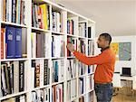 Man selecting book from bookshelf side view Stock Photo - Premium Royalty-Free, Artist: Cultura RM, Code: 613-00909361