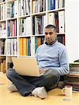 Man leaning against bookshelf, laptop computer on lap, portrait Stock Photo - Premium Royalty-Free, Artist: Blend Images, Code: 613-00909461