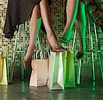 Women Sitting on Stools with Shopping Bags