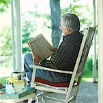 Man Reading Newspaper on Front Porch