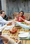 Family Making Toasts At Dinner Outdoors