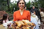 Woman Holding Platter Of Food At Dinner Outdoors