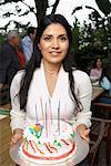 Woman Holding Birthday Cake At Party Outdoors    Stock Photo - Premium Rights-Managed, Artist: Masterfile, Code: 700-00918153