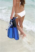 Young girl walking with snorkel equipment along the beach Stock Photo - Premium Royalty-Freenull, Code: 628-00919196