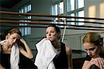 Exhausted female ballet dancers with towels sitting on the floor