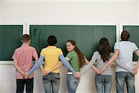 A group of teenagers standing in front of blackboard and holding hands Stock Photo - Premium Royalty-Freenull, Code: 628-00920608