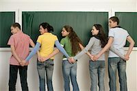 A group of teenagers standing in front of blackboard, holding hands Stock Photo - Premium Royalty-Freenull, Code: 628-00920651
