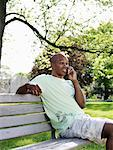 Man Sitting on Park Bench Using Cellular Telephone    Stock Photo - Premium Royalty-Free, Artist: Masterfile, Code: 600-00948557