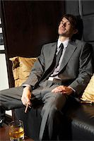 Man Sitting on Sofa with Cigar and Liquor Stock Photo - Premium Royalty-Freenull, Code: 600-00984353