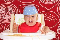 Baby in High Chair with Spaghetti Bowl on Head    Stock Photo - Premium Royalty-Freenull, Code: 600-01015395